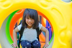 Asian kid girl having fun to play on children`s climbing toy at school playground,back to school outdoor activity stock photos
