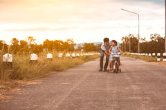 Asian kid girl having fun to ride bicycle with father Stock Photos