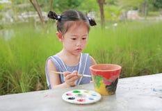 Asian kid girl paint on earthenware dish.  stock image