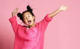 Asian kid girl in pink sweater, white pants and funny buns sings singing dancing on pink royalty free stock photography