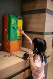 Asian kid girl using public wire telephone on wooden desk royalty free stock photography