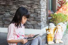 Asian kid girl using tablet for online learning. Little asian kid girl using tablet device for online learning and reading information. Daylight outdoor Royalty Free Stock Photos