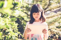 Asian kid girl using tablet play game. Little asian kid girl using modern tablet device watching video and play game. Daylight outdoor garden trees, blur in Stock Images