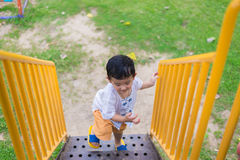 Asian kid goes up the stairs in the park. concept of growing up. Step by step the child rises higher and goes further Stock Photo