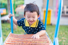 Asian kid goes up the stairs in the park. concept of growing up. Step by step the child rises higher and goes further Royalty Free Stock Photos
