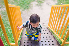 Asian kid goes up the stairs in the park. concept of growing up. Step by step the child rises higher and goes further, shallow DOF Royalty Free Stock Photography