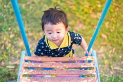 Asian kid goes up the stairs in the park. concept of growing up. Step by step the child rises higher and goes further. under sunset light Stock Photography