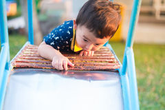 Asian kid goes up the stairs in the park. concept of growing up. Step by step the child rises higher and goes further. under sunset light Royalty Free Stock Photo