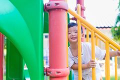 Asian kid goes up the stairs in the park. concept of growing up. Step by step the child rises higher and goes further Royalty Free Stock Images