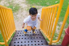 Asian kid goes up the stairs in the park. concept of growing up. Step by step the child rises higher and goes further Royalty Free Stock Photo