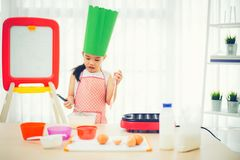 Asian kid having fun with cooking and preparing the dough, bake cookies in the kitchen.  Stock Photo