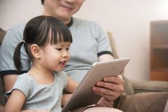 Asian kid and her father sitting and using digital tablet togeth. Asian little kid girl and her father sitting and using digital tablet together. Knowledge and Stock Photo