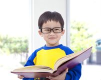 Asian kid holding book. Asian kid smiling and holding book royalty free stock photos