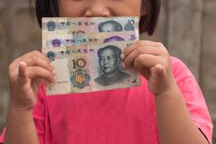 Kid holding Chinese money. Asian kid holding Chinese money Yuan Royalty Free Stock Photography
