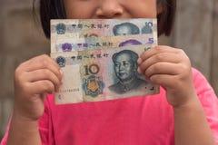 Kid holding Chinese money. Asian kid holding Chinese money Yuan Royalty Free Stock Photo