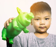 Asian kid is holding green piggy bank Stock Photos