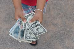 Asian kid holding money cash. Dollars,yuan in top angle view Royalty Free Stock Photography