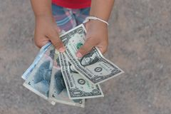 Asian kid holding money cash. Dollars,yuan in top angle view Royalty Free Stock Image