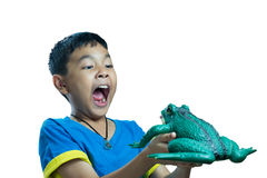 Asian kid holding toy frog and look very scare. On white background Royalty Free Stock Photos