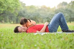 Asian kid is kissing on her father face. Asian little kid is kissing on her father face while they are sleeping on the grass in nature at park outdoor. Family royalty free stock photo