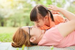 Asian kid is kissing to her young mother. Asian little kid is kissing to her young mother while they are lying on the grass in nature at park outdoor. Family royalty free stock photography