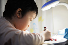 Asian kid learning. A little Chinese kid doing her homework Stock Photography