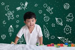 Asian kid learning by playing with his imagination about science and space adventure, hand drawn on the green chalkboard,. Education back to school and stock photos