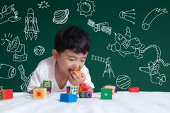 Asian kid learning by playing with his imagination about science and space adventure, hand drawn on the green chalkboard,. Education back to school and royalty free stock images