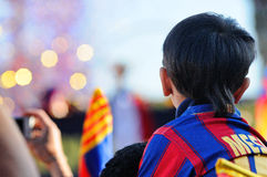 An asian kid with Lionel Messi's shirt, awaits hopefully the arrival of their idols of F.C Barcelona soccer team Royalty Free Stock Image