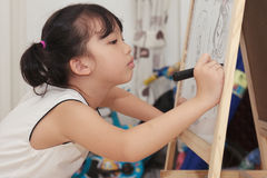 Asian kid painting. An asian kid painting on the white board Royalty Free Stock Photography