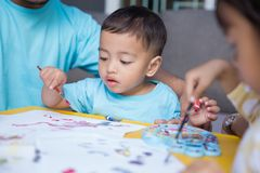 Asian kid painting and drawing. Happy little asian kid painting and drawing at home using water color paint Royalty Free Stock Photography