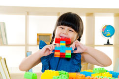 Asian kid. Piling up building blocks royalty free stock photography