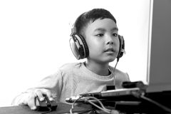Asian kid play computer games (black and white). Asian kid play computer internet games and wear headset to communicate Royalty Free Stock Image