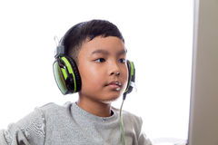 Asian kid play computer games (closeup shot). Asian kid play computer internet games and wear headset to communicate Royalty Free Stock Photo