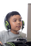 Asian kid play computer games (closeup shot). Asian kid play computer internet games and wear headset to communicate Royalty Free Stock Image