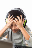 Asian kid play computer games with disappointed gesture. Asian kid play computer internet games and wear headset to communicate Stock Photo