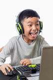 Asian kid play computer games with funny face. Asian kid play computer internet games and wear headset to communicate Stock Photo