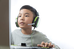 Asian kid play computer games. Asian kid play computer internet games and wear headset to communicate Royalty Free Stock Photo