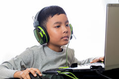 Asian kid play computer games. Asian kid play computer internet games and wear headset to communicate Stock Photo