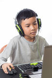 Asian kid play computer games. Asian kid play computer internet games and wear headset to communicate Royalty Free Stock Photos