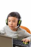 Asian kid play computer games. Asian kid play computer internet games and wear headset to communicate Royalty Free Stock Image