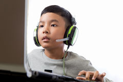 Asian kid play computer games Royalty Free Stock Photos