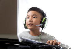 Asian kid play computer games. Asian kid play computer internet games and wear headset to communicate Royalty Free Stock Photography