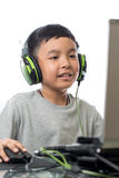 Asian kid play computer games with smile on his face. Asian kid play computer internet games and wear headset to communicate Stock Image