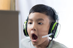 Asian kid play computer games with surprising face. Asian kid play computer internet games and wear headset to communicate Stock Photo
