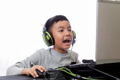 Asian kid play computer games and talking with friend. Asian kid play computer internet games and wear headset to communicate Stock Photo