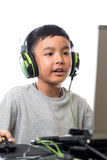 Asian kid play computer games and talking with friend. Asian kid play computer internet games and wear headset to communicate Stock Photography