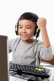 Asian kid play computer games with victory gesture. Asian kid play computer internet games and wear headset to communicate Stock Photos
