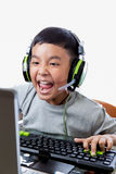 Asian kid play computer games with yelling face. Asian kid play computer internet games and wear headset to communicate Royalty Free Stock Photos