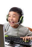 Asian kid play computer games with yelling face. Asian kid play computer internet games and wear headset to communicate Stock Images